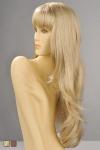Perruque longue et l�g�rement ondulante avec une frange droite effil�e qui souligne le regard, en blond ou chatain.